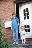 Παιδιά που αφήνουν το σπίτι την πρώτη ημέρα στο σχολείο Στοκ φωτογραφία με δικαίωμα ελεύθερης χρήσης