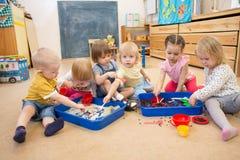 Παιδιά που βελτιώνουν τις δεξιότητες μηχανών των χεριών με το ρύζι και τα φασόλια Στοκ Φωτογραφία