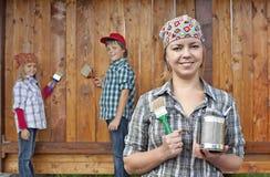 Παιδιά που βοηθούν τη μητέρα τους που χρωματίζει το ξύλινο υπόστεγο Στοκ Φωτογραφίες