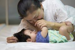 Παιδιά που βρίσκονται σε ένα κρεβάτι με τη μητέρα του για να φροντίσει την αγάπη και τη ζεστασιά στοκ φωτογραφία με δικαίωμα ελεύθερης χρήσης