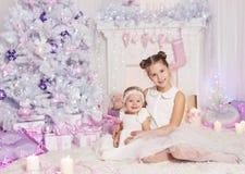 Παιδιά που γιορτάζουν τις διακοπές Χριστουγέννων, χριστουγεννιάτικο δέντρο κοριτσάκι παιδιών στοκ φωτογραφίες