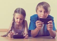 Παιδιά που εξετάζουν την οθόνη των smartphones στοκ εικόνα