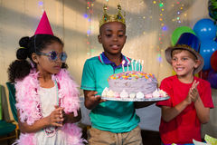 Παιδιά που εξετάζουν το κέικ που κατέχει το αγόρι Στοκ Φωτογραφίες