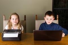 Παιδιά που εργάζονται στην παλαιά γραφομηχανή και το lap-top Στοκ Φωτογραφίες