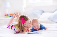 Παιδιά που διαβάζουν στην άσπρη κρεβατοκάμαρα Στοκ φωτογραφίες με δικαίωμα ελεύθερης χρήσης