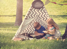 Παιδιά που διαβάζουν τα βιβλία έξω στη σκηνή Teepee στοκ φωτογραφία με δικαίωμα ελεύθερης χρήσης