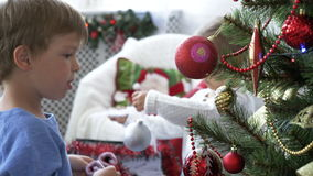 Παιδιά που διακοσμούν το χριστουγεννιάτικο δέντρο στο ελαφρύ δωμάτιο στην ημέρα απόθεμα βίντεο