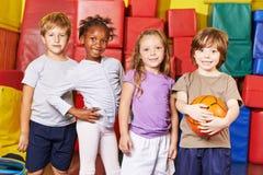 Παιδιά που διαμορφώνουν την ομάδα για το παιχνίδι σφαιρών στη γυμναστική Στοκ Εικόνα