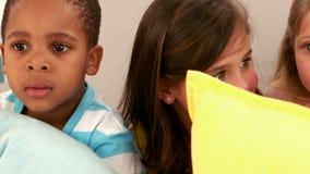 Παιδιά που κάθονται στον καναπέ με τα μαξιλάρια απόθεμα βίντεο