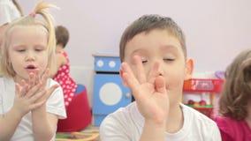 Παιδιά που κάθονται τα κυματίζοντας χέρια στη κάμερα απόθεμα βίντεο