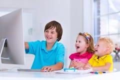 Παιδιά που κάνουν την εργασία με το σύγχρονο υπολογιστή στοκ φωτογραφία