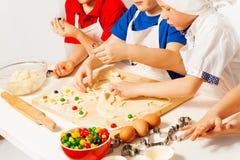 Παιδιά που κατασκευάζουν γεμισμένα τα καραμέλα μπισκότα στο ξύλινο γραφείο Στοκ εικόνα με δικαίωμα ελεύθερης χρήσης