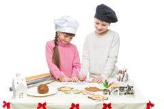Παιδιά που κατασκευάζουν τα μπισκότα Χριστουγέννων στοκ φωτογραφία