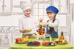 Παιδιά που κατασκευάζουν τα πρόχειρα φαγητά φρούτων στοκ εικόνες