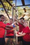 Παιδιά που κρατούν ένα σχοινί κατά τη διάρκεια της κατάρτισης σειράς μαθημάτων εμποδίων Στοκ εικόνα με δικαίωμα ελεύθερης χρήσης