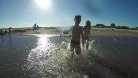 Παιδιά που κρατούν τα χέρια τρέχοντας στο νερό απόθεμα βίντεο