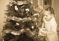 Παιδιά που κρεμούν τις διακοσμήσεις στο έλατο Στοκ εικόνες με δικαίωμα ελεύθερης χρήσης