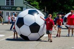 Παιδιά που κυλούν τις γιγαντιαίες σφαίρες ποδοσφαίρου Στοκ εικόνα με δικαίωμα ελεύθερης χρήσης