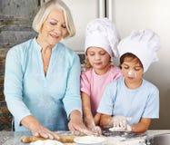 Παιδιά που μαγειρεύουν με τη γιαγιά Στοκ φωτογραφία με δικαίωμα ελεύθερης χρήσης