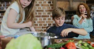 Παιδιά που μαγειρεύουν τα τρόφιμα μαζί στην κουζίνα με τους γονείς που αγκαλιάζουν το κρασί κατανάλωσης, ευτυχής οικογένεια που π απόθεμα βίντεο