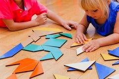 Παιδιά που μαθαίνουν - παιχνίδι μικρών παιδιών και κοριτσιών με τις γεωμετρικές μορφές Στοκ Εικόνα