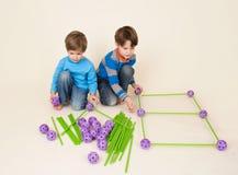 Παιδιά που μοιράζονται το σύνολο κατασκευής, χτίζοντας τα κομμάτια στοκ εικόνα με δικαίωμα ελεύθερης χρήσης