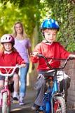 Παιδιά που οδηγούν τα ποδήλατα στο δρόμο τους στο σχολείο με τη μητέρα Στοκ Φωτογραφίες