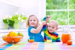 Παιδιά που πίνουν το χυμό από πορτοκάλι Στοκ φωτογραφία με δικαίωμα ελεύθερης χρήσης
