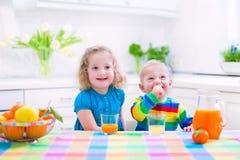 Παιδιά που πίνουν το χυμό από πορτοκάλι στοκ φωτογραφία