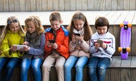Παιδιά που παίζουν με τα κινητά τηλέφωνα Στοκ Φωτογραφία