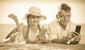 Παιδιά που παίζουν με τα κινητά τηλέφωνα Στοκ Φωτογραφίες