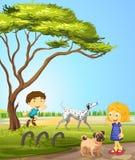 Παιδιά που παίζουν με τα σκυλιά στο πάρκο ελεύθερη απεικόνιση δικαιώματος