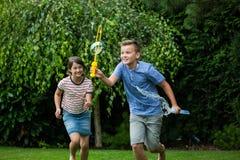 Παιδιά που παίζουν με τις φυσαλίδες στο πάρκο Στοκ εικόνες με δικαίωμα ελεύθερης χρήσης