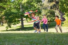 Παιδιά που παίζουν με τον ικτίνο στο πάρκο Στοκ φωτογραφία με δικαίωμα ελεύθερης χρήσης
