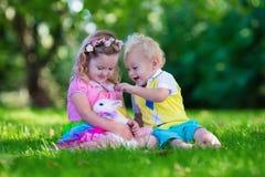 Παιδιά που παίζουν με το κουνέλι κατοικίδιων ζώων Στοκ φωτογραφία με δικαίωμα ελεύθερης χρήσης