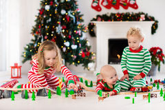 Παιδιά που παίζουν με το σιδηρόδρομο παιχνιδιών στο πρωί Χριστουγέννων Στοκ εικόνες με δικαίωμα ελεύθερης χρήσης