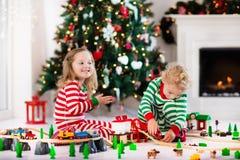 Παιδιά που παίζουν με το σιδηρόδρομο παιχνιδιών στο πρωί Χριστουγέννων Στοκ φωτογραφία με δικαίωμα ελεύθερης χρήσης