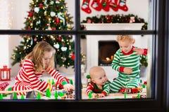 Παιδιά που παίζουν με το σιδηρόδρομο παιχνιδιών στο πρωί Χριστουγέννων Στοκ Εικόνες