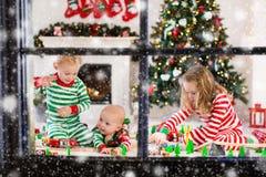 Παιδιά που παίζουν με το σιδηρόδρομο παιχνιδιών στο πρωί Χριστουγέννων Στοκ Φωτογραφία