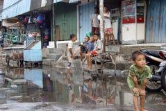 Παιδιά που παίζουν σε μια πλημμυρισμένη οδό Στοκ Φωτογραφίες