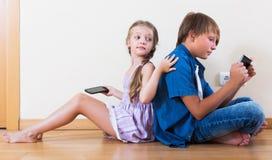 Παιδιά που παίζουν στα κινητά τηλέφωνα Στοκ φωτογραφίες με δικαίωμα ελεύθερης χρήσης