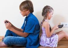 Παιδιά που παίζουν στα κινητά τηλέφωνα Στοκ Φωτογραφία