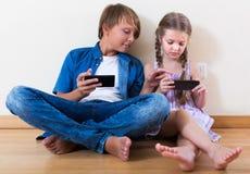 Παιδιά που παίζουν στα κινητά τηλέφωνα Στοκ εικόνες με δικαίωμα ελεύθερης χρήσης