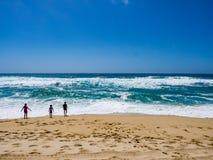 Παιδιά που παίζουν στα μεγάλα κύματα Στοκ Εικόνες