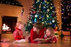 Παιδιά που παίζουν στην εστία στη Παραμονή Χριστουγέννων στοκ εικόνα με δικαίωμα ελεύθερης χρήσης