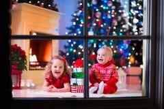Παιδιά που παίζουν στην εστία στη Παραμονή Χριστουγέννων στοκ εικόνες