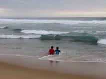 Παιδιά που παίζουν στην κυματωγή Στοκ Φωτογραφίες