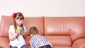 Παιδιά που παίζουν στον καναπέ κορίτσι με το κάτω σύνδρομο αποκατάσταση των ατόμων με ειδικές ανάγκες απόθεμα βίντεο