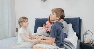 Παιδιά που παίζουν στο κρεβάτι γονέων ενώ η μητέρα και ο πατέρας χρησιμοποιούν το έξυπνο τηλέφωνο κυττάρων, ευτυχής οικογένεια μα απόθεμα βίντεο