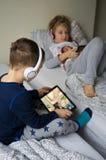 Παιδιά που παίζουν στο κρεβάτι με τις ταμπλέτες και τα τηλέφωνά τους Στοκ φωτογραφία με δικαίωμα ελεύθερης χρήσης